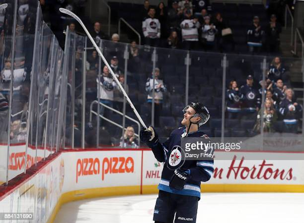 Nikolaj Ehlers of the Winnipeg Jets gets set to send a souvenir stick over the glass after receiving second star honors following a 74 victory over...
