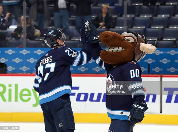 Nikolaj Ehlers of the Winnipeg Jets high fives mascot Mick E Moose following a 74 victory over the Vegas Golden Knights at the Bell MTS Place on...