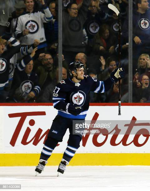 Nikolaj Ehlers of the Winnipeg Jets lifts his stick as he celebrates a first period goal by teammate Bryan Little against the Carolina Hurricanes at...