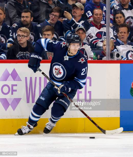 Nikolaj Ehlers of the Winnipeg Jets plays the puck along the boards during second period action against the Minnesota Wild at the Bell MTS Place on...