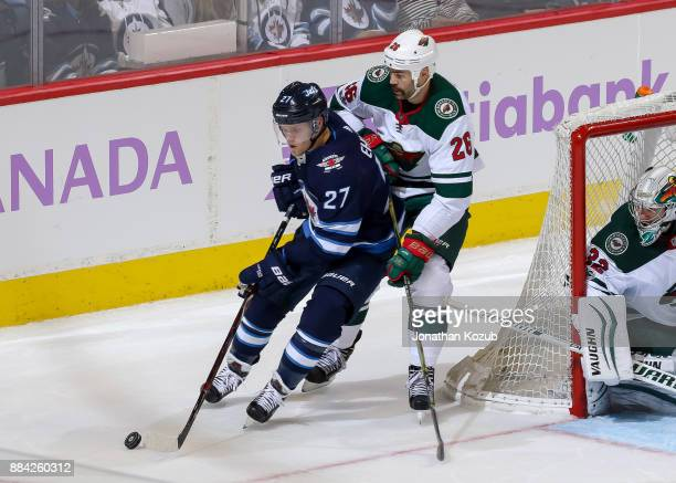 Nikolaj Ehlers of the Winnipeg Jets plays the puck away from Daniel Winnik of the Minnesota Wild during third period action at the Bell MTS Place on...