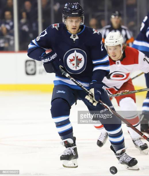 Nikolaj Ehlers of the Winnipeg Jets plays the puck down the ice during first period action against the Carolina Hurricanes at the Bell MTS Place on...