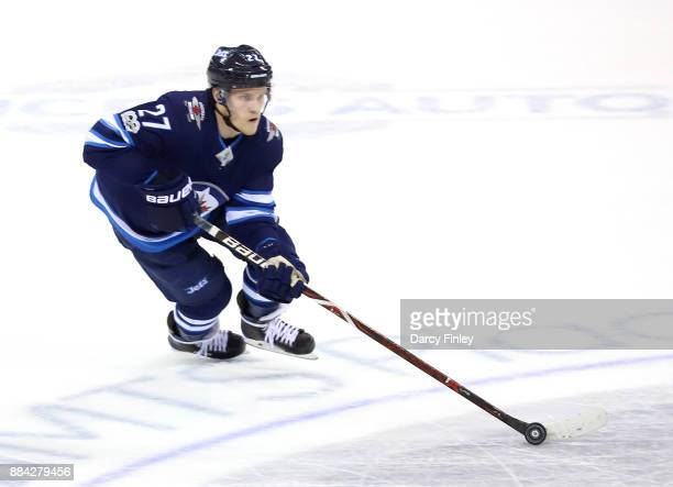 Nikolaj Ehlers of the Winnipeg Jets plays the puck up the ice during second period action against the Minnesota Wild at the Bell MTS Place on...
