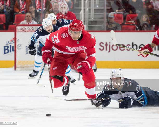 Nikolaj Ehlers of the Winnipeg Jets reaches for the puck in front of Andreas Athanasiou of the Detroit Red Wings during an NHL game at Little Caesars...