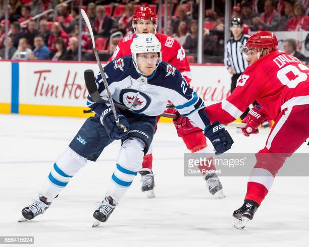 Nikolaj Ehlers of the Winnipeg Jets tries to skate past the defense of Trevor Daley of the Detroit Red Wings during an NHL game at Little Caesars...