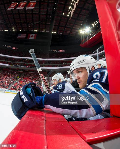 Nikolaj Ehlers of the Winnipeg Jets watches the action from the bench against the Detroit Red Wings during an NHL game at Little Caesars Arena on...