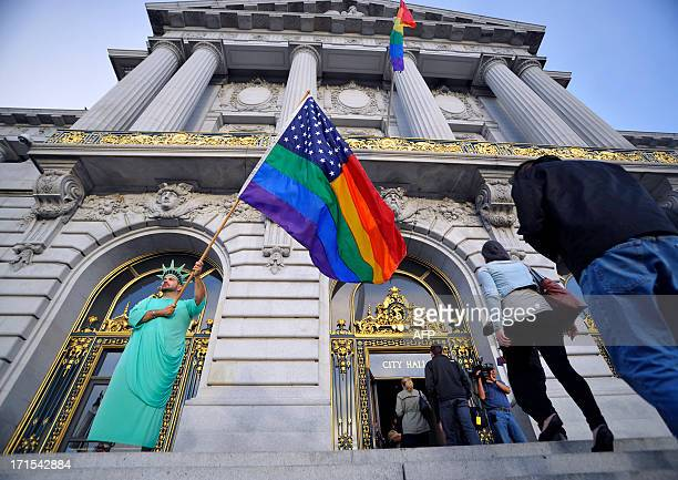 Nikolas Lemos waves a rainbow flag as people enter San Francisco City Hall in anticipation of The US Supreme Court ruling on gay marriage on June 26...