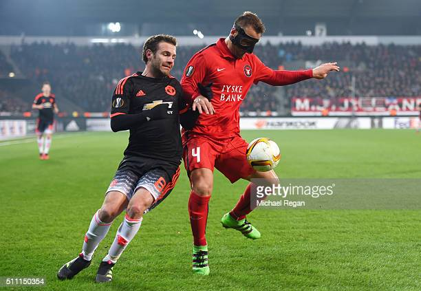 Nikolay Bodurov of FC Midtjylland and Juan Mata of Manchester United compete for the ball during the UEFA Europa League round of 32 first leg match...