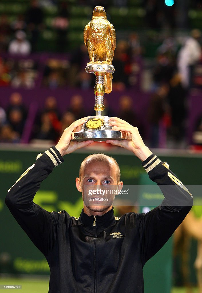 Nikolay Davydenko of Russia celebrates with the trophy following victory over Rafael Nadal of Spain in the Final match of the ATP Qatar ExxonMobil...