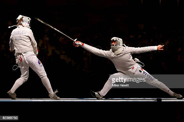Nikolay Kovalev of Russia and Giampiero Pastore of Italy compete in the men's team sabre fencing bronze medal match at the Fencing Hall of National...