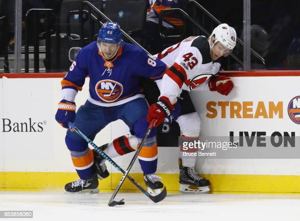 Nikolay Kulemin of the New York Islanders and Ben Thomson of the New Jersey Devils battle for the puck during the third period during a preseason...