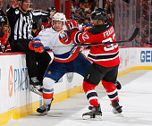 Nikolay Kulemin of the New York Islanders and Mark Fraser of the New Jersey Devils come together at the boards during the game at the Prudential...