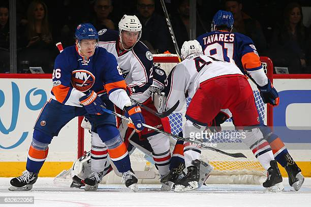 Nikolay Kulemin of the New York Islanders and Ryan Murray of the Columbus Blue Jackets battle for the puck at the Barclays Center on January 24 2017...