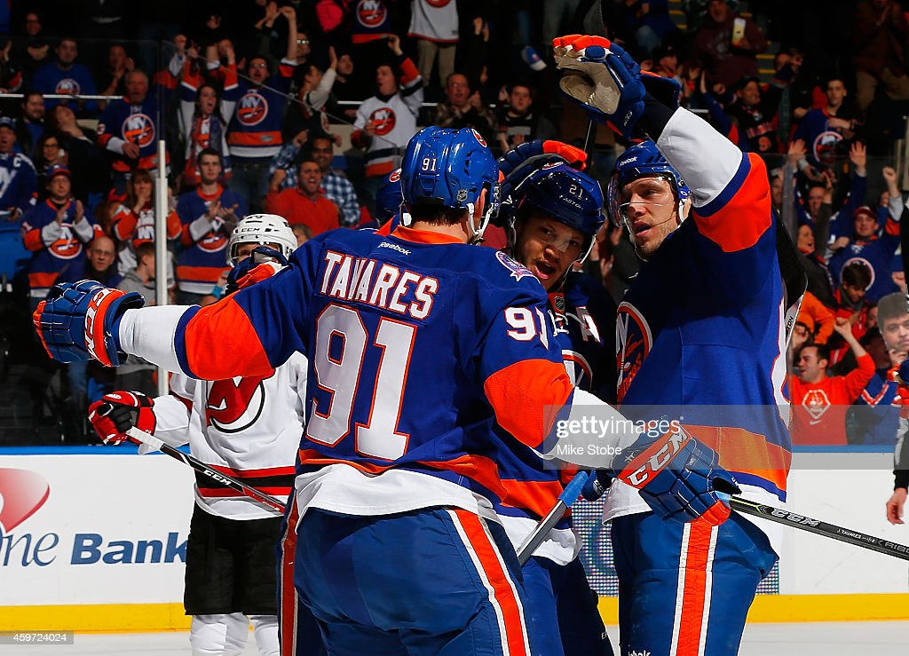 Nikolay Kulemin #86 of the New York Islanders celebrates his first period goal with teammates <a gi-track='captionPersonalityLinkClicked' href=/galleries/search?phrase=John+Tavares&family=editorial&specificpeople=601791 ng-click='$event.stopPropagation()'>John Tavares</a> #91 and <a gi-track='captionPersonalityLinkClicked' href=/galleries/search?phrase=Kyle+Okposo&family=editorial&specificpeople=540469 ng-click='$event.stopPropagation()'>Kyle Okposo</a> #21 against the New Jersey Devils at Nassau Veterans Memorial Coliseum on November 29, 2014 in Uniondale, New York.