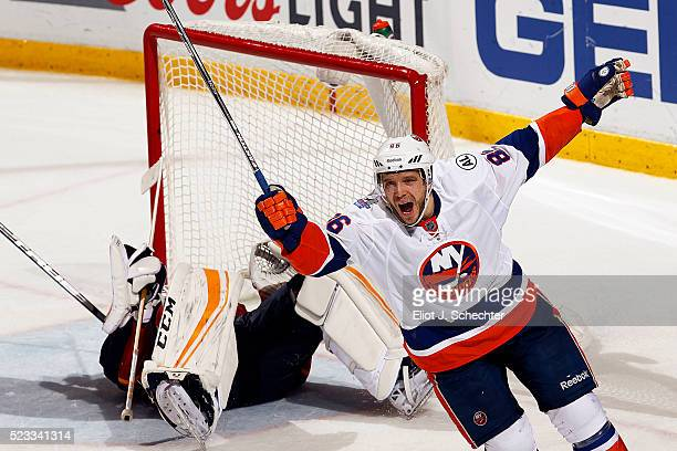 Nikolay Kulemin of the New York Islanders celebrates his teammate Alan Quine scoring the winning goal in the second overtime period against...