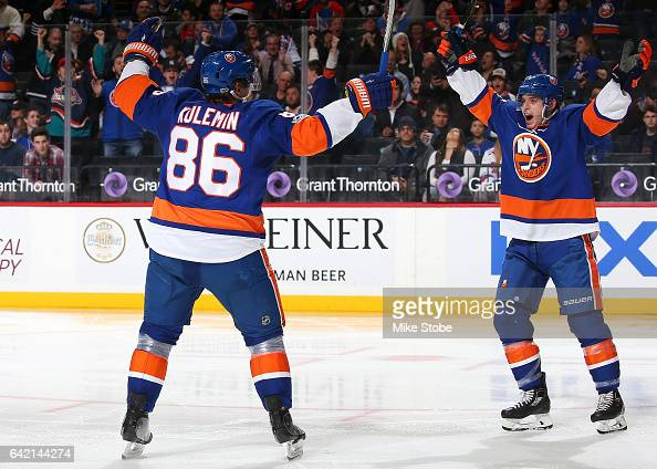 Nikolay Kulemin of the New York Islanders celebrates his third period goal against the New York Rangers with teammate Thomas Hickey at the Barclays...