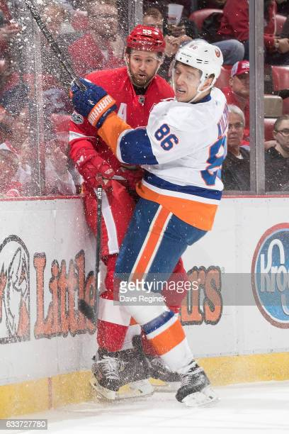 Nikolay Kulemin of the New York Islanders checks Niklas Kronwall of the Detroit Red Wings into the boards during an NHL game at Joe Louis Arena on...