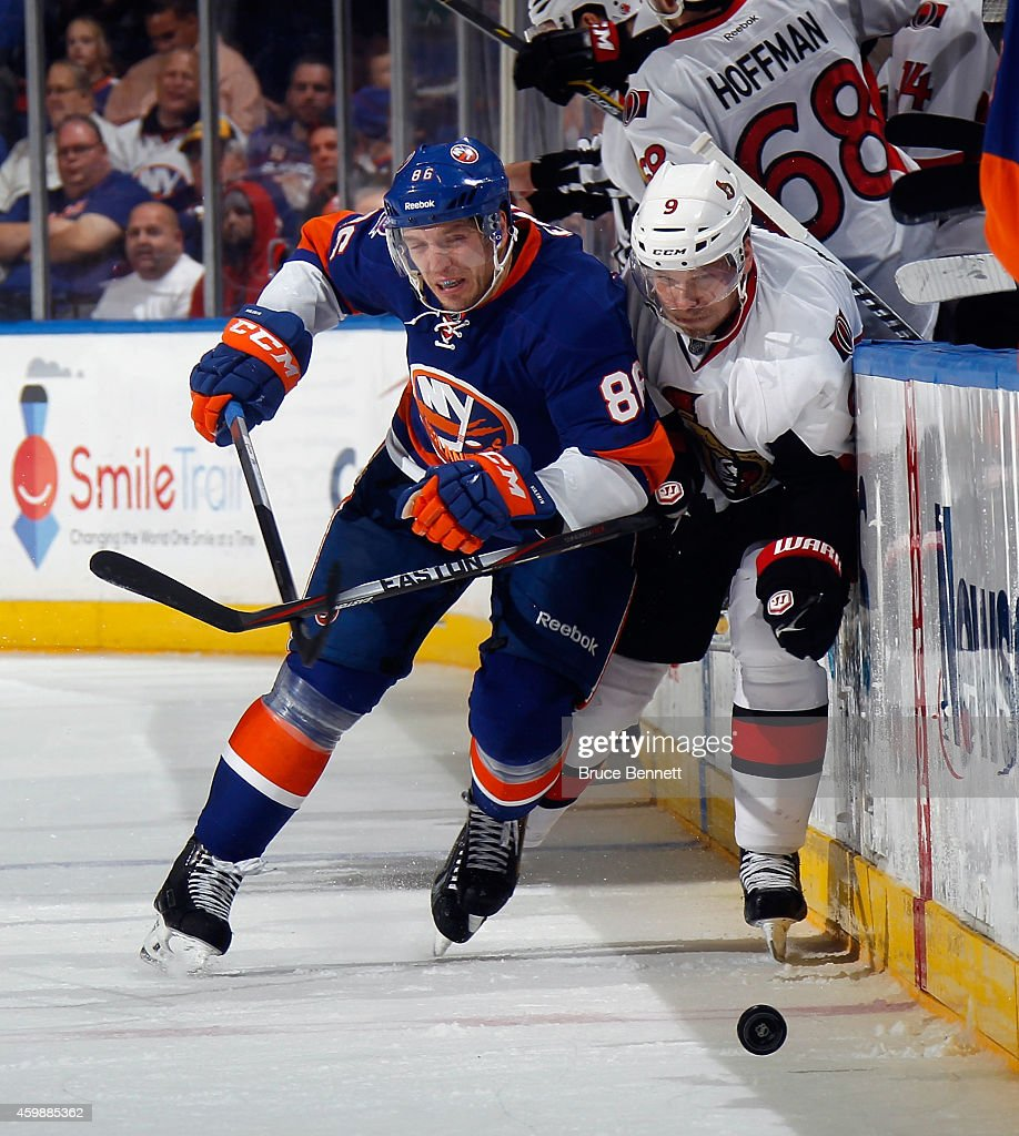 Nikolay Kulemin of the New York Islanders hits Milan Michalek of the Ottawa Senators at the Nassau Veterans Memorial Coliseum on December 2 2014 in...