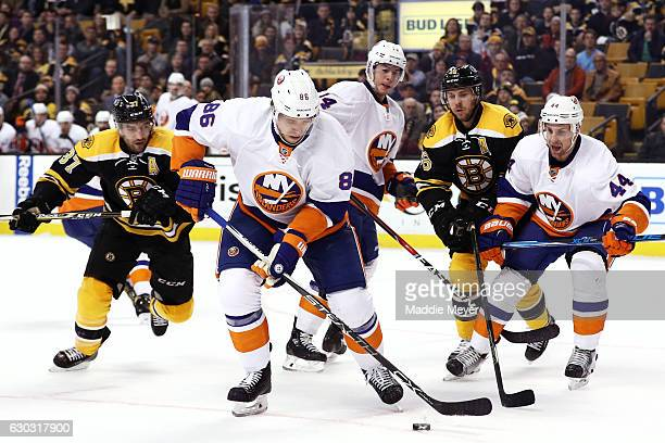Nikolay Kulemin of the New York Islanders looks to clear the puck with pressure from Patrice Bergeron of the Boston Bruins during the first period at...