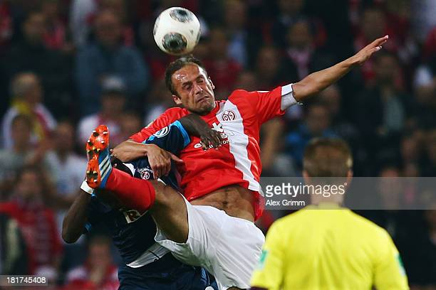 Nikolce Noveski of Mainz jumps for a header with Anthony Ujah of Koeln during the DFB Cup second round match between 1 FSV Mainz 05 and 1 FC Koeln at...