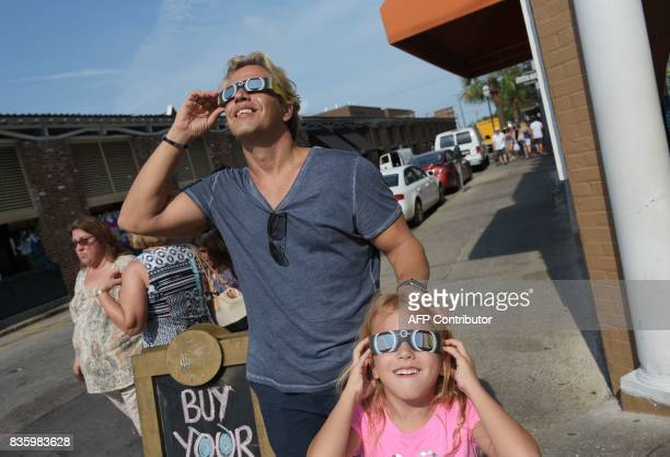 Nikos Spyridonos and his daughter Zoe try out eclipse glasses ahead of the total solar eclipse in Charleston South Carolina on August 20 2017 / AFP...