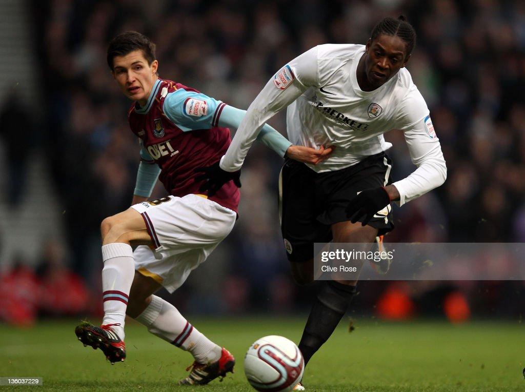 Nile Ranger of Barnsley (R) is challenged by Daniel Potts of West Ham United during the npower Championship match between West Ham United and Barnsley at the Boleyn Ground on December 17, 2011 in London, England.