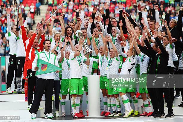 Nilla Fischer and team mates of Wolfsburg celebrate with the trophy after winning the Women's DFB Cup Final between Turbine Potsdam and VfL Wolfsburg...