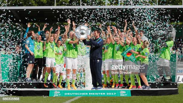 Nilla Fischer of VfL Wolfsburg and head coach Ralf Kellermann of VfL Wolfsburg lift the Championship trophy in celebration of the German Championship...