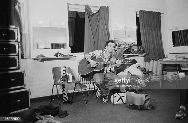 Nils Lofgren US rock singersongwriter and guitarist sitting on a chair while playing an acoustic guitar in Guildford Surrey England Great Britain in...