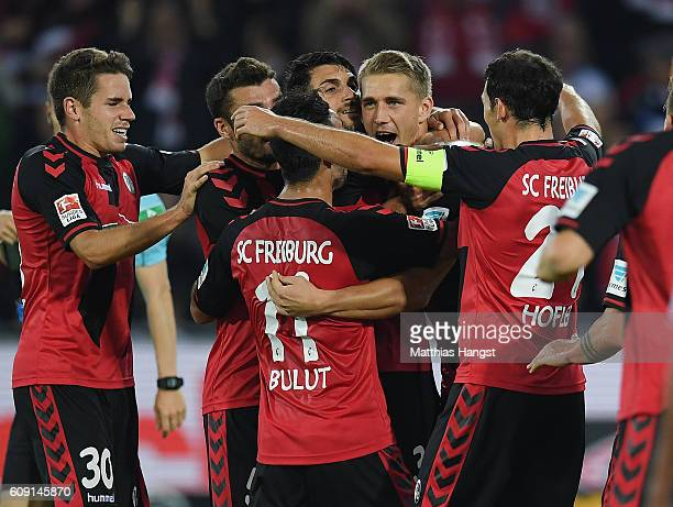 Nils Petersen of Freiburg celebrates with his teammates after scoring his team's first goal during the Bundesliga match between SC Freiburg and...