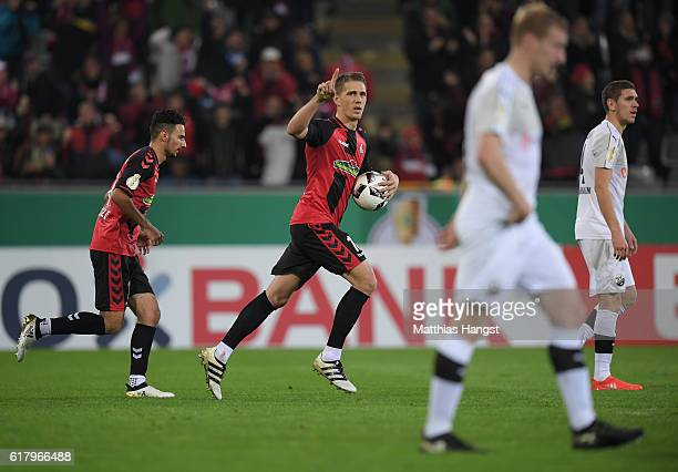 Nils Petersen of Freiburg celebrates with his teammates after scoring his team's third goal by penalty during the DFB Cup match between SC Freiburg...