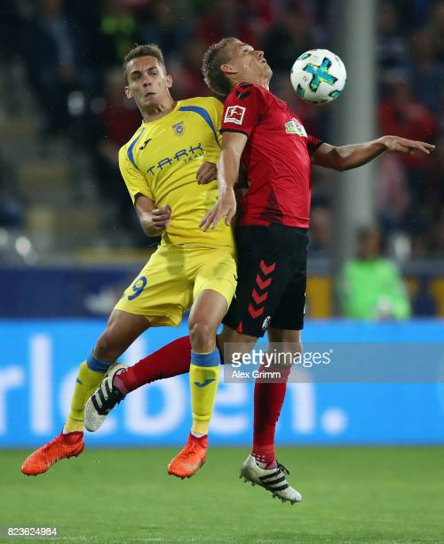 Nils Petersen of Freiburg is challenged by Jure Balkovec of Domzale during the UEFA Europa League Third Qualifying Round first leg match between SC...