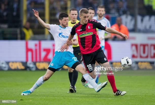 Nils Petersen of Freiburg is challenged by KlaasJan Huntelaar of Schalke during the Bundesliga match between SC Freiburg and FC Schalke 04 at...