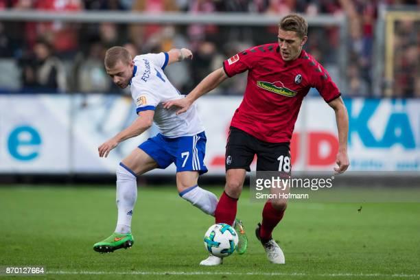 Nils Petersen of Freiburg is challenged by Max Meyer of Schalke during the Bundesliga match between SportClub Freiburg and FC Schalke 04 at...