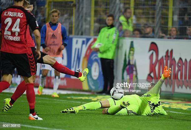 Nils Petersen of Freiburg scores his team's first goal past goalkeeper Rene Adler of Hamburg during the Bundesliga match between SC Freiburg and...