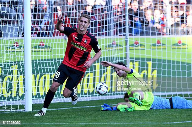 Nils Petersen of SC Freiburg celebrates his goal against Paul Verhaegh and Marvin Hitz of FC Augsburg during the Bundesliga match between Sport Club...
