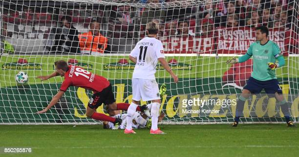 Nils Petersen of SC Freiburg shoots for Freiburg against Felix Klaus and Goalkeeper Philipp Tschauner of Hannover 96 during the Bundesliga match...