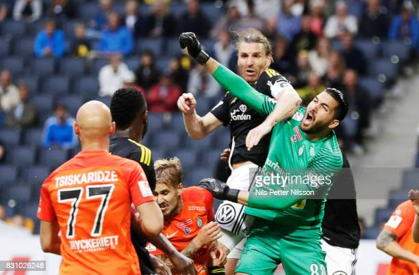 NilsEric Johansson of AIK hits Alireza Haghighi goalkeeper of Athletic FC Eskilstuna with his elbow during the Allsvenskan match between AIK and...