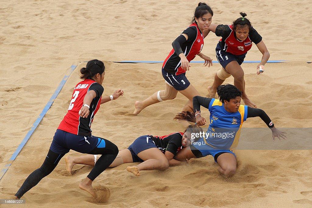 Nimashi Kokila Edirising Edirisinhage (R) of Sri Lanka is tackled as he competes during the Beach Kabaddi Women's Team Group A match between Sri Lanka and Thailand on Day 4 of the 3rd Asian Beach Games Haiyang 2012 at Fengxiang Beach on June 20, 2012 in Haiyang, China.