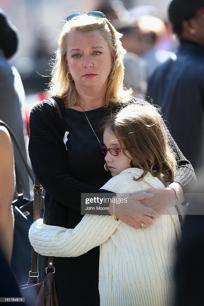 Nina Fisher (L), sister of 9/11 victim Andrew Fisher, embraces her niece Mia Tinson, 9, during ceremonies for the eleventh anniversary of the terrorist attacks on lower Manhattan at the World Trade Center on September 11, 2012 in New York City. New York City and the nation are commemorating the eleventh anniversary of the September 11, 2001 attacks which resulted in the deaths of nearly 3,000 people after two hijacked planes crashed into the World Trade Center, one into the Pentagon in Arlington, Virginia and one crash landed in Shanksville, Pennsylvania.