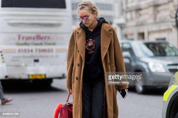Nina Suess wearing brown wool coat hoody red Fendi bag outside Preen during London Fashion Week September 2017 on September 17 2017 in London England