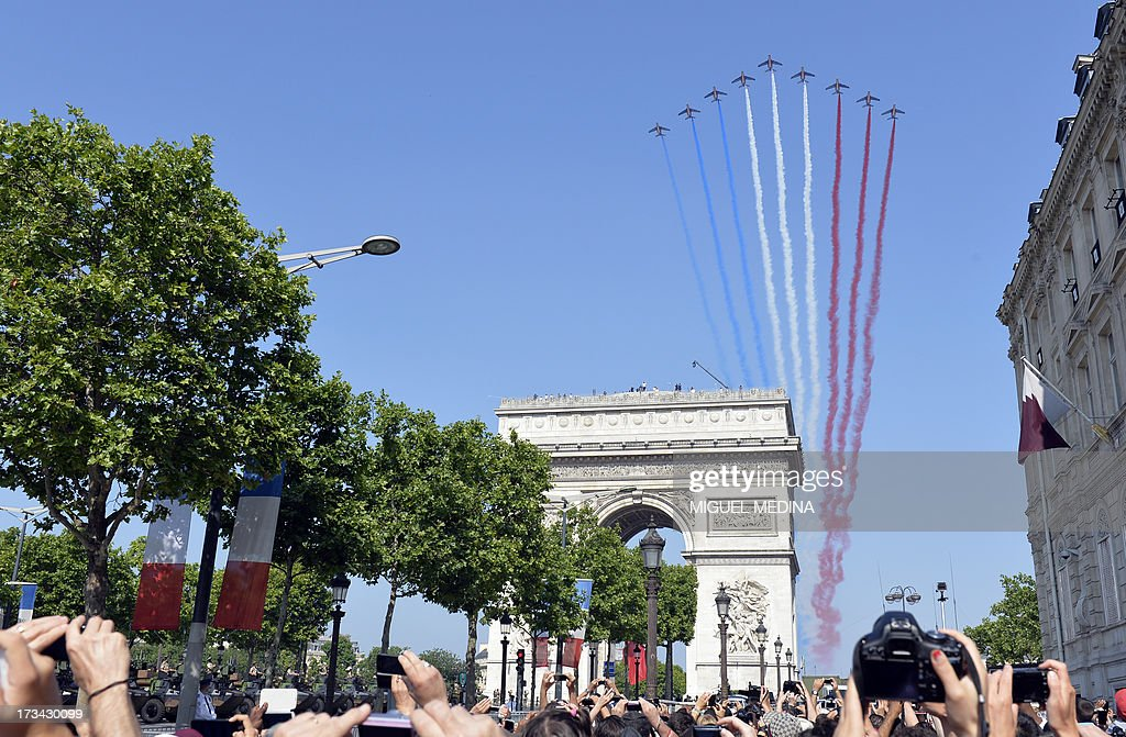 Nine alphajets from the French Air Force Patrouille de France releasing trails of red white and blue smoke colors of French national flag fly over...