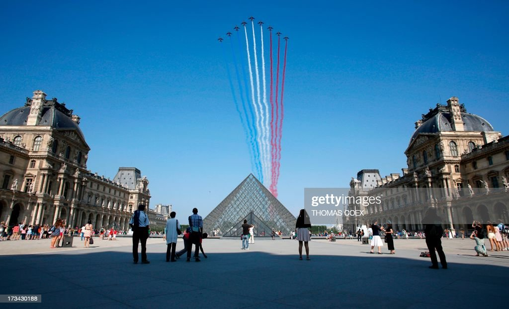 Nine alphajets from the French Air Force Patrouille de France releasing trails of red, white and blue smoke, colors of French national flag, fly over the Pyramid du Louvre during the Bastille Day parade, on July 14, 2013 in Paris.