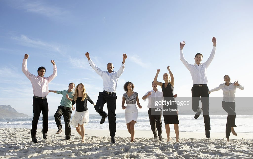 Nine businessmen and women jumping on beach, smiling : Stock Photo
