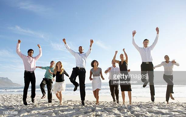 Nine businessmen and women jumping on beach, smiling