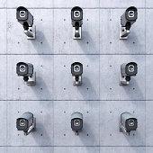 Nine CCTV cameras on concrete wall