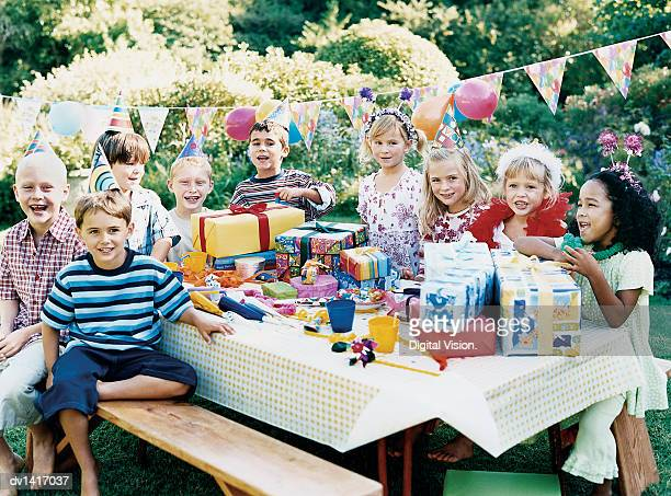 Nine Children Sitting at a Table at a Birthday Party
