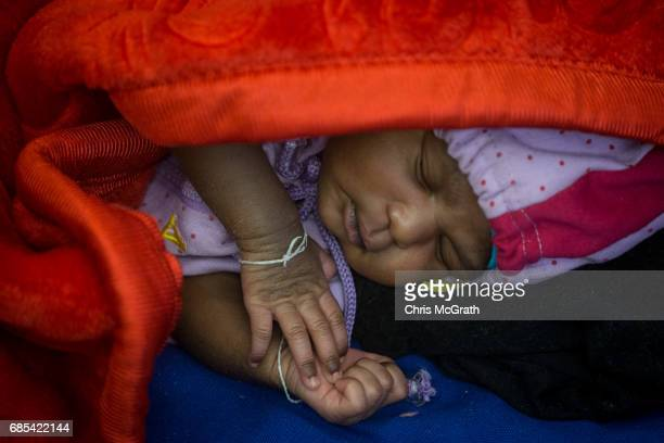 A nine day old baby that was rescued at sea yesterday sleeps in the medical clinic on board the Migrant Offshore Aid Station 'Phoenix' vessel on May...