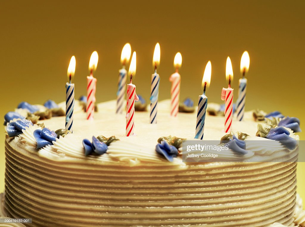Nine lit candles and blue decorative flowers on birthday cake : Stock Photo