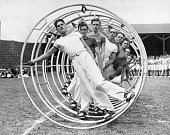 Nine men exercising in a hoopla wheel a long metal rolling jungle gym Undated navy photograph